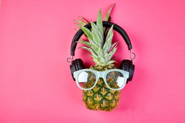 Piatto disteso di ananas alla moda, faccia buffa con cuffie e occhiali da sole.