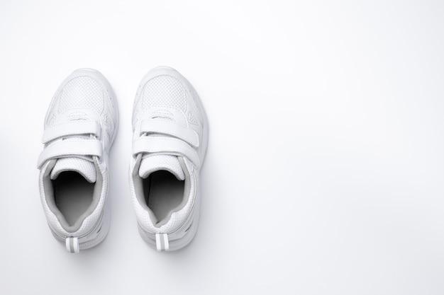 Flat due sneakers bianche da ragazza con chiusure in velcro isolate su uno sfondo bianco