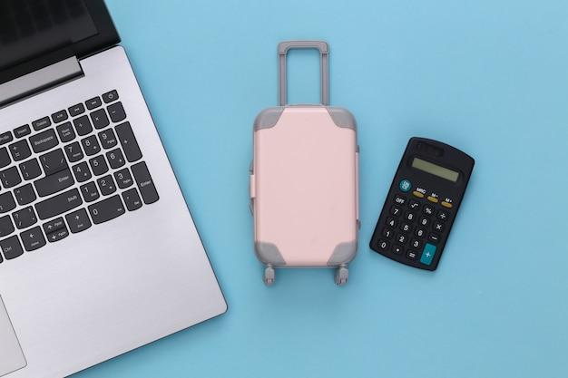 Vacanza di vacanza piatta e concetto di planata di viaggio. laptop e mini valigia da viaggio in plastica, calcolatrice su sfondo blu. vista dall'alto