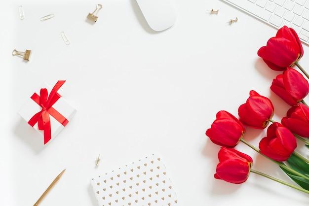 Fondo piatto di san valentino con tastiera del computer, regalo, tazza da caffè e spazio bianco della copia di vista superiore del tulipano rosso. sfondo per un blogger o un ufficio