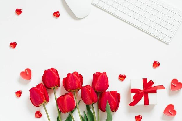Fondo piatto di san valentino con tastiera del computer, regalo, tazza da caffè e spazio bianco della copia di vista superiore del tulipano rosso
