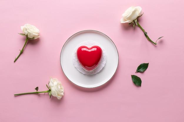 Concetto di giorno di san valentino piatto laico con torta cuore rosso e fiori di rosa. sfondo rosa. copia spazio
