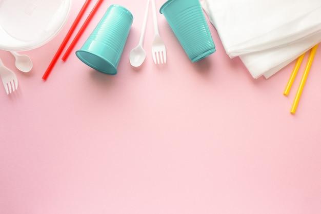 Disposizione piatta di varie stoviglie in plastica usa e getta su sfondo rosa, spazio per il testo