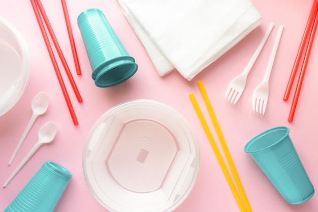 Disposizione piatta di varie stoviglie in plastica usa e getta su sfondo rosa, vista dall'alto.