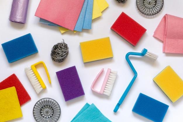Lay piatto di vari articoli per la pulizia e la casa su sfondo bianco, vista dall'alto.