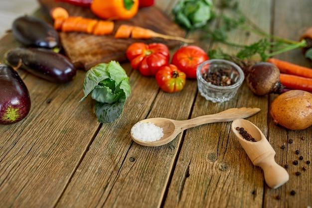 Disposizione piana di vari ingredienti di verdure biologiche e piccanti su fondo di legno, cibo locale, cibo vegetariano e vegano, concetto di primavera dietetica, vista dall'alto, spazio copia.