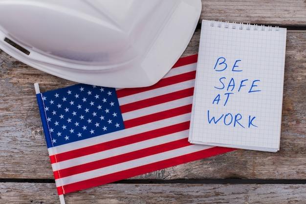 Flat lay avvertendo i lavoratori dei costruttori americani di essere al sicuro sul lavoro. casco bianco con bandiera degli stati uniti e blocco note sul tavolo di legno invecchiato.