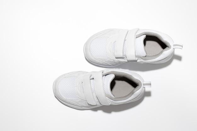 Scarpe da corsa per bambini bianche piatte che imitano la camminata con ombre dure isolate su uno sfondo bianco...