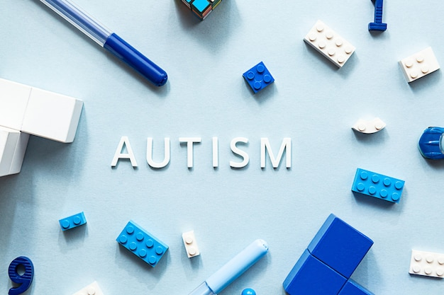 Piatto giaceva la parola bianca autismo con cubi puzzle pennarelli colorati e giocattoli
