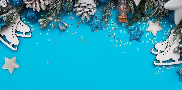 Intestazione invernale piatta: ramoscelli di abete nella neve con decorazioni natalizie nei colori blu, argento, bianco