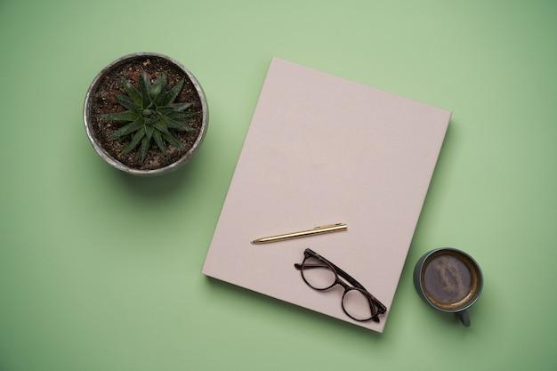 Lay piatto di con libro, tazza di caffè, occhiali da lettura, penne e matite su verde