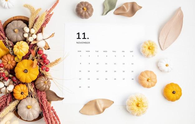 Piatto disteso con calendario per novembre con decorazione della tavola autunnale. arredamento floreale per le vacanze autunnali con zucche fatte a mano. flatlay, vista dall'alto