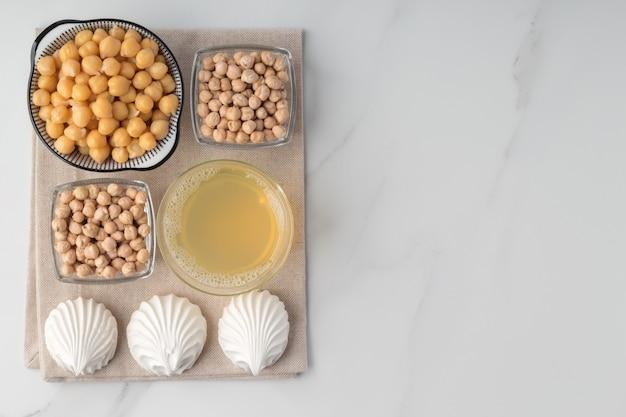 Piatto con aquafaba di ceci e meringhe su un panno da cucina su un tavolo di marmo con spazio per le copie