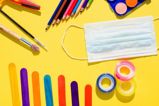 Lay piatto con il concetto di ritorno a scuola protetto con maschere igieniche.