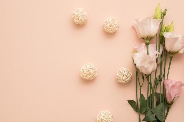 Lay piatto con fiori delicati e palline di rattan disposte su sfondo di pesca