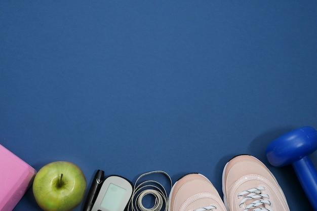 Piatto disteso con il concetto di perdita di peso dieta diabete scarpe da ginnastica, metro a nastro, glucometro su un blu