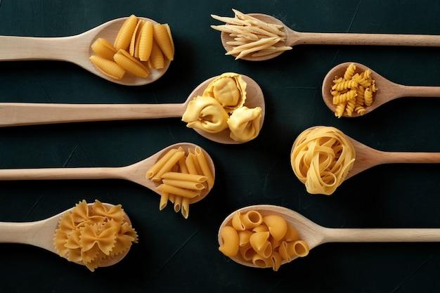 Lay piatto con diversi tipi di pasta italiana tradizionale. penne, tagliatelle, fusilli, farfalle, spaghetti e altri. concetto di cucina italiana tradizionale. vista dall'alto