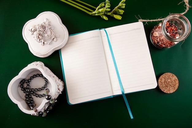 Piatto disteso con accessori femminili collana di perle in una bara, un quaderno aperto e un fiore su un verde