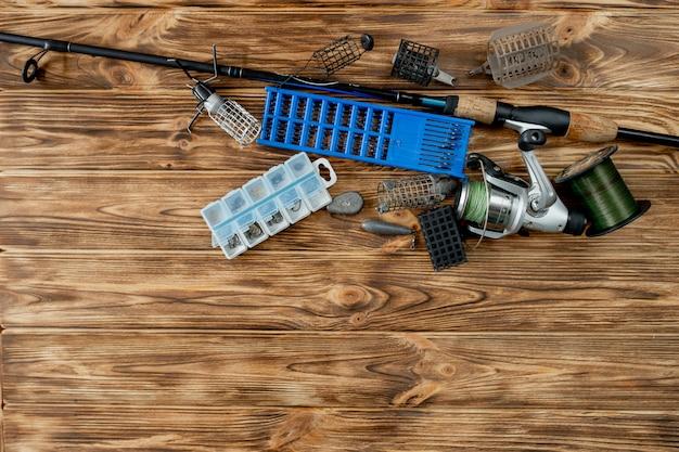 Piatto disteso con attrezzatura da pesca, canna da pesca e scatola di plastica con attrezzatura da pesca e ganci, alimentatori su assi di legno, spazio di copia