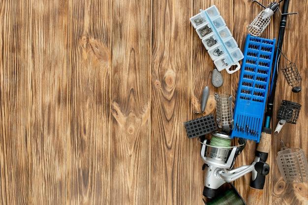 Lay piatto con attrezzatura da pesca, canna da pesca e scatola di plastica con attrezzatura da pesca e ganci
