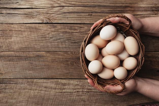 Piatto disteso con le mani che tengono cesto con uova di gallina biologiche su fondo di legno concetto di famiglia biologica con uova di galline allevate a terra e al pascolo