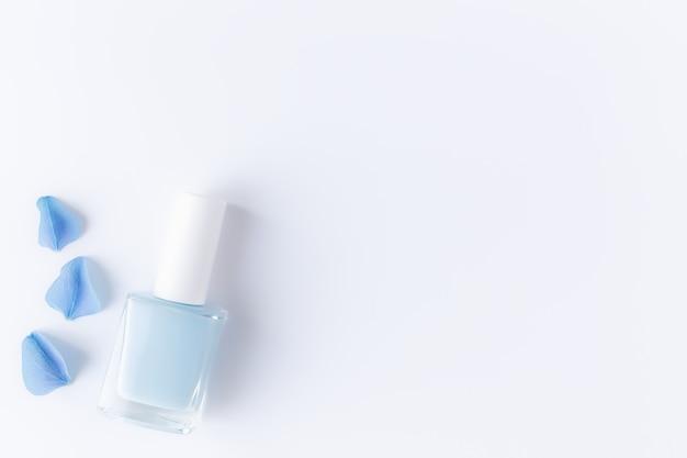 Lay piatto con petali di ortensia blu con smalto blu in una bottiglia di vetro trasparente. concetto di manicure e pedicure naturale