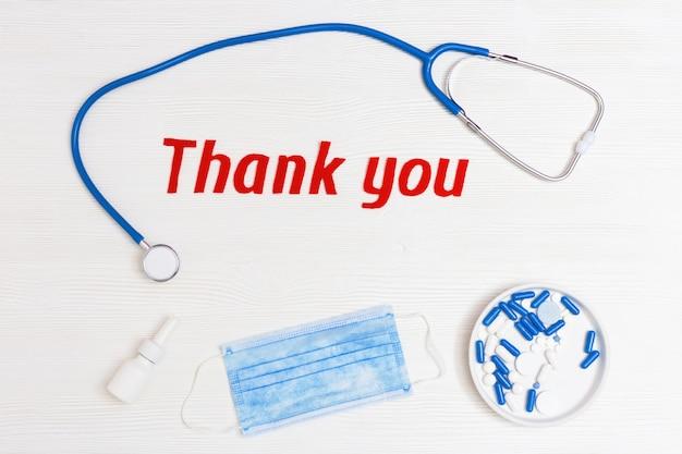 Laici piatta con stetoscopio medico, pillole, maschera monouso e testo grazie