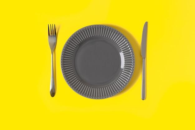 Lay piatto con mock up lastra grigia e posate su sfondo giallo alla moda con spazio di copia