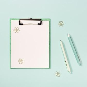 Lay piatto con tavoletta di carta mockup con clip di penne colorate blu e bianche graffette in metallo