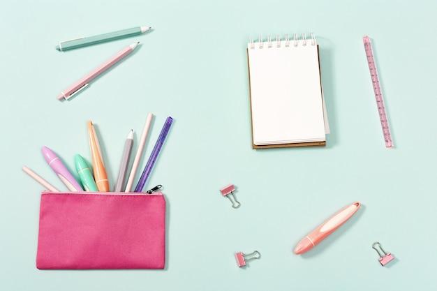 Lay piatto con notebook e cancelleria per ragazza per la scuola o il disegno righello di matite di penne colorate