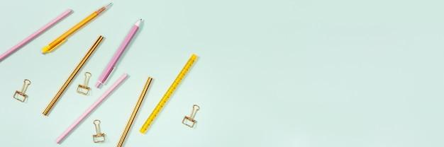 Piatto disteso con forniture per ufficio matite colorate rosa e dorate, penne e graffetta metallica metal
