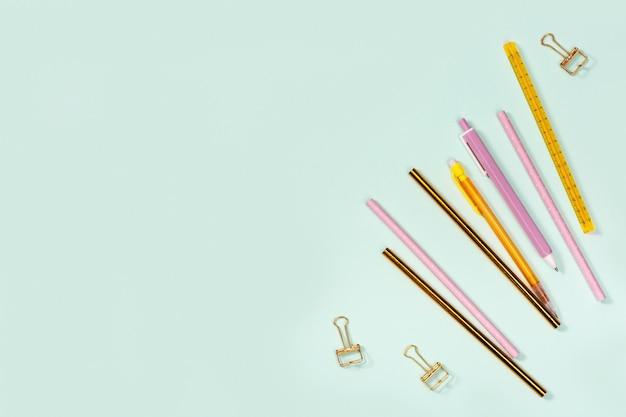 Lay piatto con forniture per ufficio, matite colorate rosa e dorate, penne e graffette metalliche. concetto di scuola e istruzione.