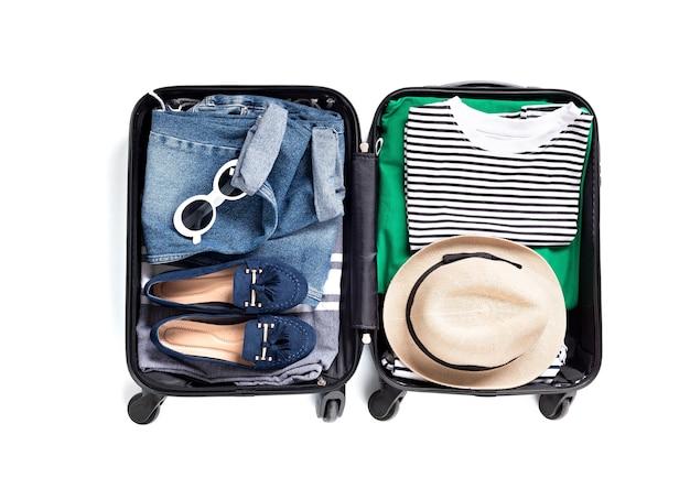 Lay piatto con valigia aperta con abiti casual per le vacanze estive sul muro bianco. vacanze estive, viaggi, turismo, concetto di bagaglio di volo. vista dall'alto