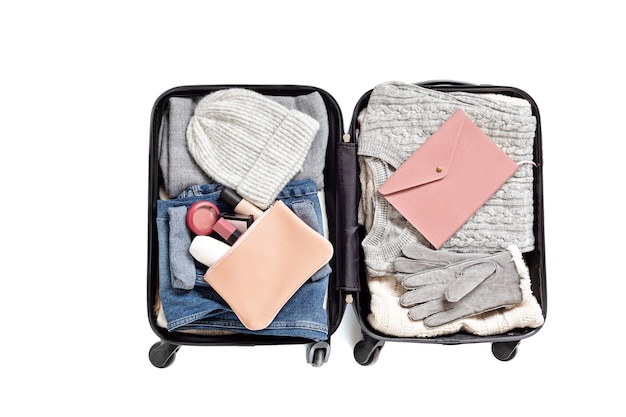 Lay piatto con valigia aperta con abiti casual