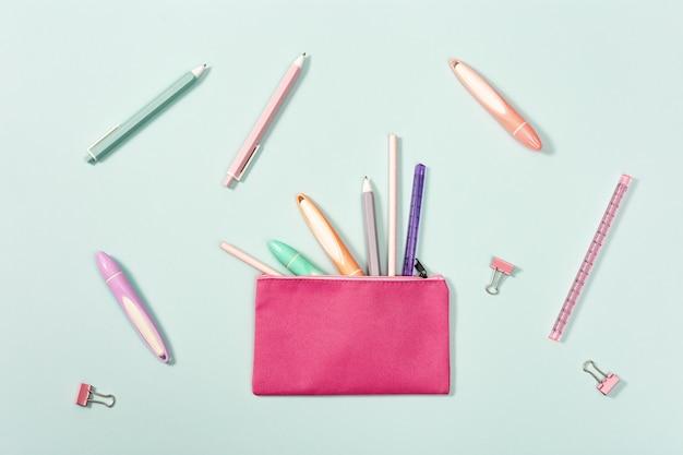 Lay piatto con astuccio con varie penne, matite, righello, pennarelli, pennarelli e graffette metalliche. concetto di scuola e istruzione per ragazza.