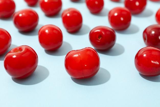 Disposizione piana con la ciliegia rossa su spazio blu, fine in su