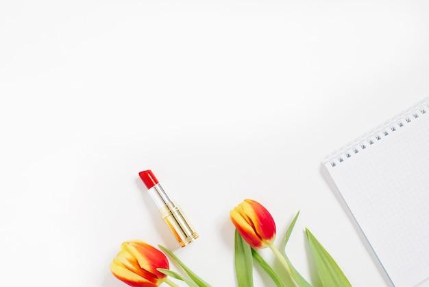 Lay piatto con tulipano rosso, taccuino e rossetto