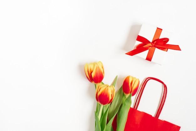 Lay piatto con tulipani gialli rossi vicino a un sacchetto di carta rosso con regalo su bianco