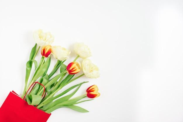 Lay piatto con tulipani rossi e gialli in un sacchetto regalo rosso su bianco