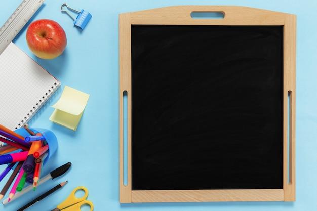 Piatto con il concetto di scuola su superficie blu con vari accessori per la scuola, penne, matita, blocco note, graffette, mela, righello, forbici, lavagna nera vuota, adesivo di carta su superficie blu