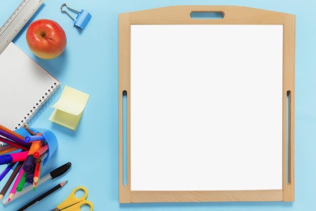 Piatto con il concetto di scuola su superficie blu con vari accessori per la scuola, penne, matita, blocco note, graffette, mela, righello, forbici, lavagna bianca vuota, adesivo di carta su superficie blu