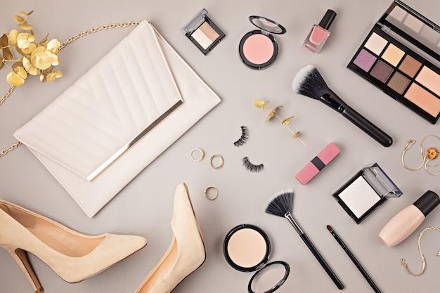 Lay piatto con set di cosmetici decorativi professionali, strumenti per il trucco e accessori donna sul muro grigio con spazio di copia. blog di bellezza, moda, festa e concetto di shopping. vista dall'alto.