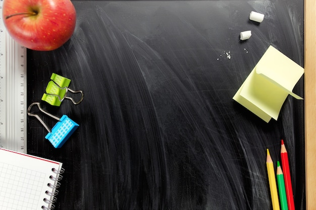 Disposizione piatta con piccola superficie nera del consiglio scolastico con accessori scolastici
