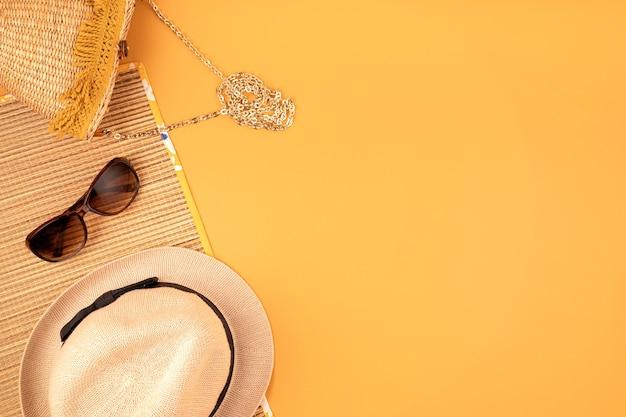 Lay piatto con accessori estivi per donna. cappello da sole, occhiali da sole ,. viaggio estivo, vacanze, concetto di protezione dal calore. copia spazio, vista dall'alto