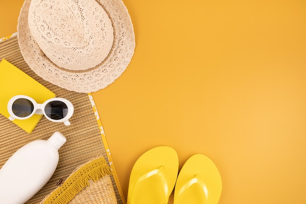 Lay piatto con accessori estivi per donna. cappello da sole, occhiali da sole, protezione solare, infradito e borsa. viaggio estivo, vacanze, concetto di protezione dal calore. copia spazio, vista dall'alto