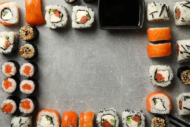 Disposizione piana con i rotoli di sushi sulla tavola grigia