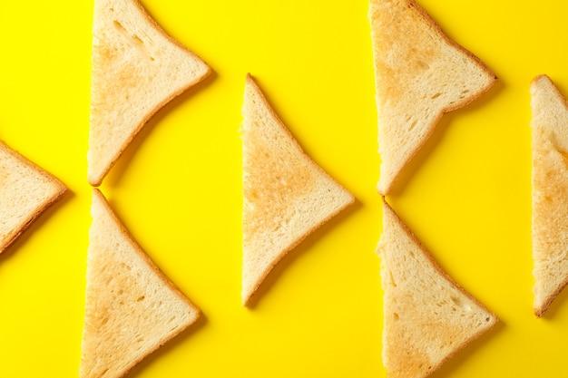 Lay piatto con pane tostato su sfondo giallo