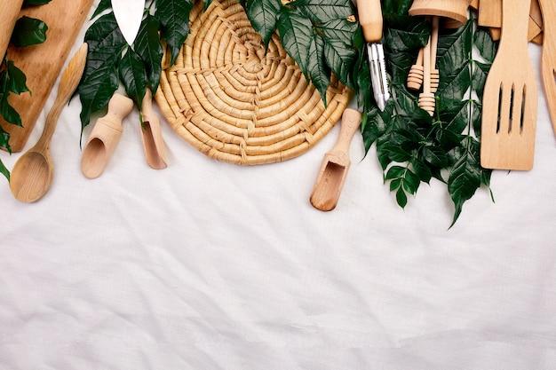 Lay piatto con utensili da cucina in legno con foglie verdi, utensili da cucina su sfondo tessile, collezione ktchenware catturata dall'alto, mockup, cornice.