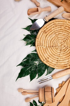 Lay piatto con utensili da cucina in legno con foglie verdi, utensili da cucina su tessuto