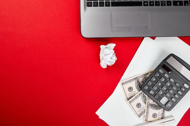 Lay piatto con area di lavoro su backgroud rosso, libero professionista online, concetto finanziario, fare soldi su internet, dollari, calcolatrice, notebook, concetto di idea di ricerca
